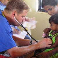 Photo: Physician with a stethoscope checking a child's vital signs