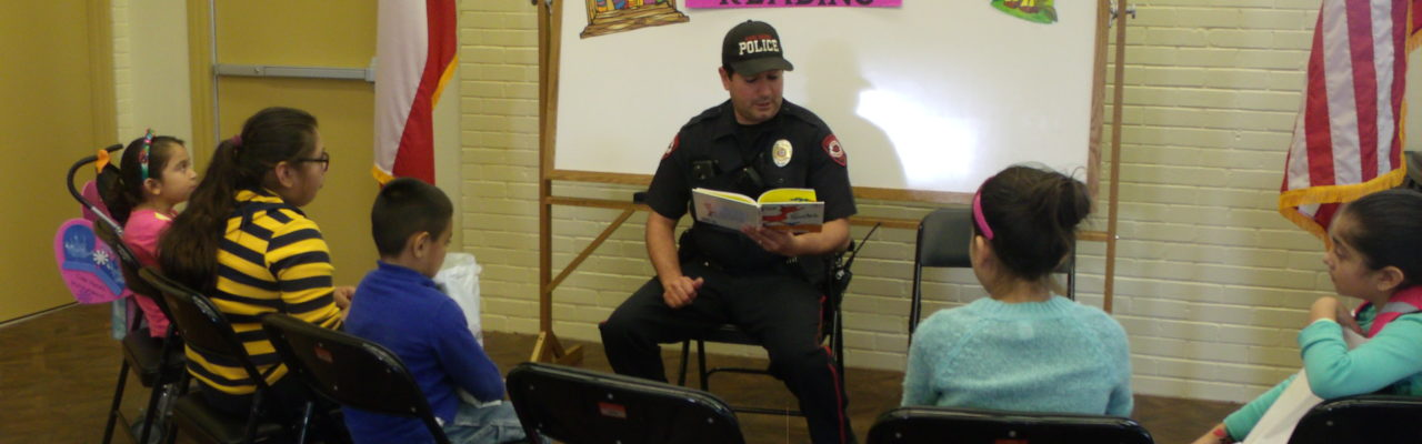 Photo: A police officer reading a book to children