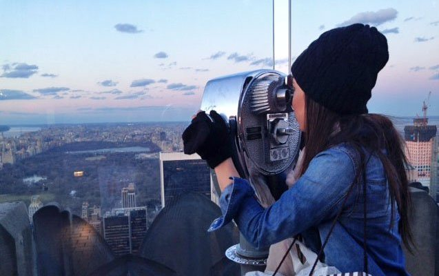 Photo: Lisa Zamora using binoculars to check out the city skyline
