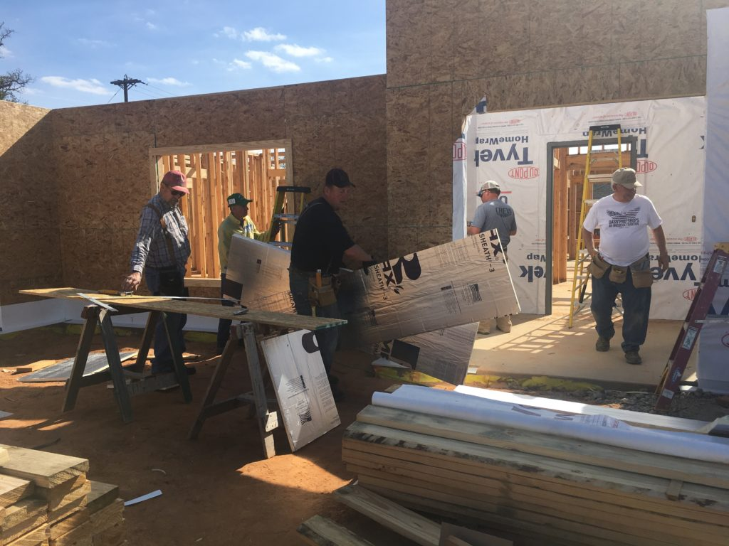 Several volunteers and workers building a new home