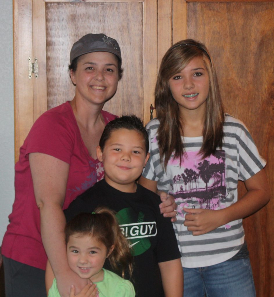 Bethany standing with her mother and siblings